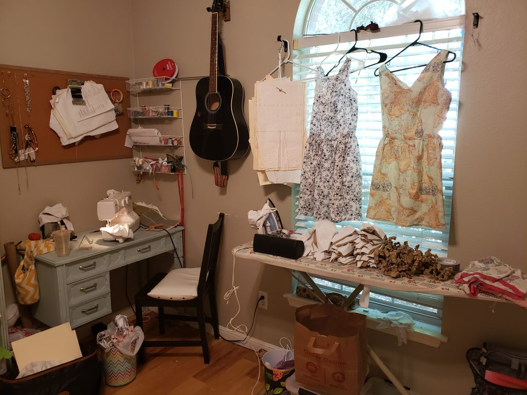 Collins' workspace before she transitioned on site. The dresses hanging on the window are her original designs.