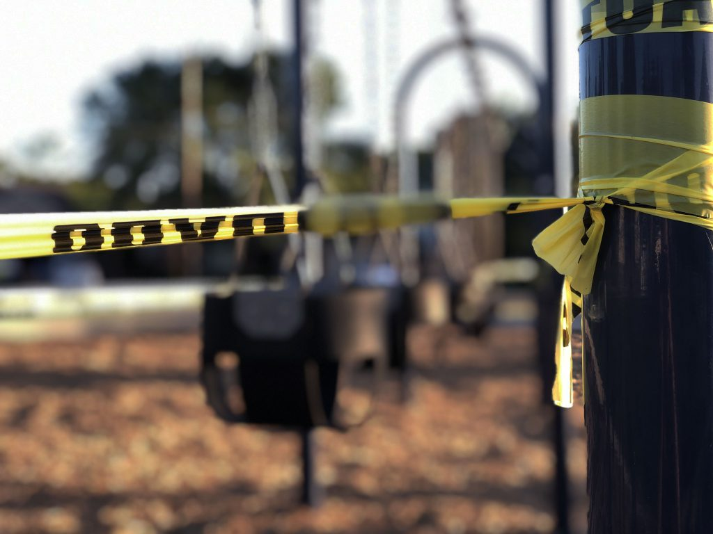 caution tape on a pole in front of a playground