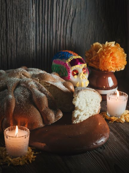 Mexican bread of the dead on clay dish with candles and flowers