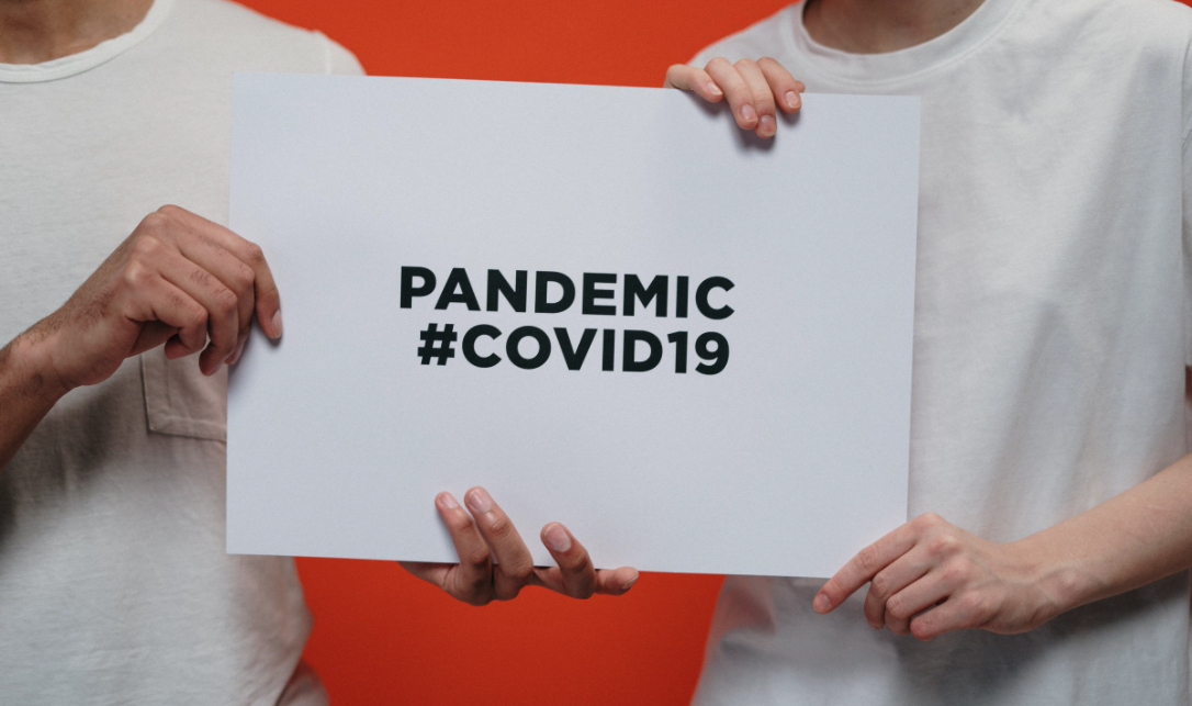 pandemic poster with covid 19 hashtag held by 2 set of hands