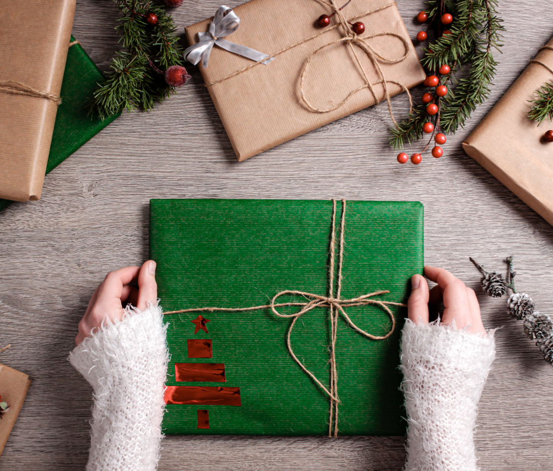 person wearing sweater wrapping a gift with green paper and twine