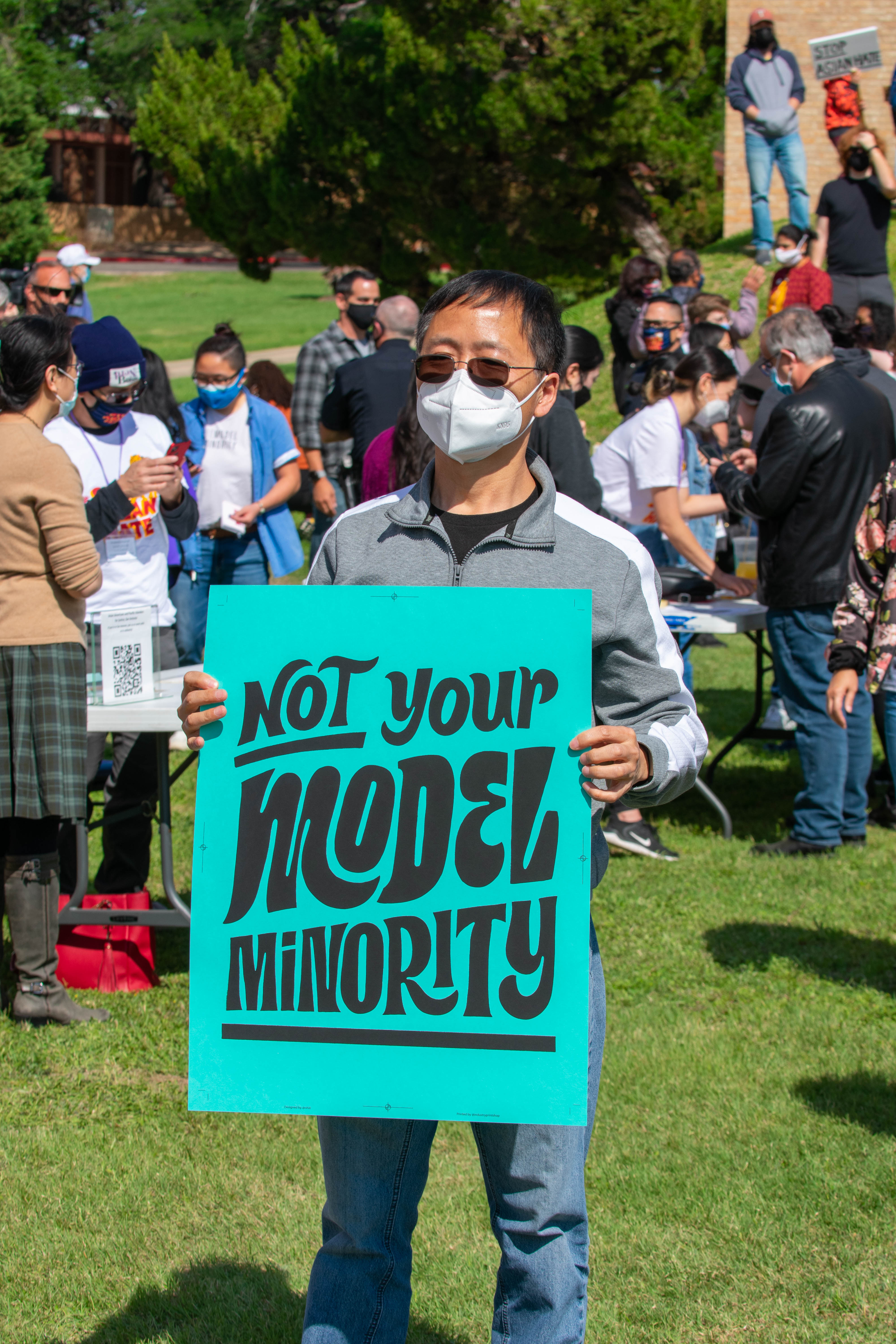 """person with teal sign """"Not Your Model Minority"""""""
