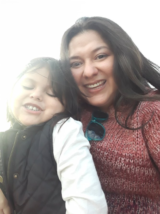 Isabel Torres smiles at the camera wearing a red sweater while her daughter sits on her lap smiling as well.