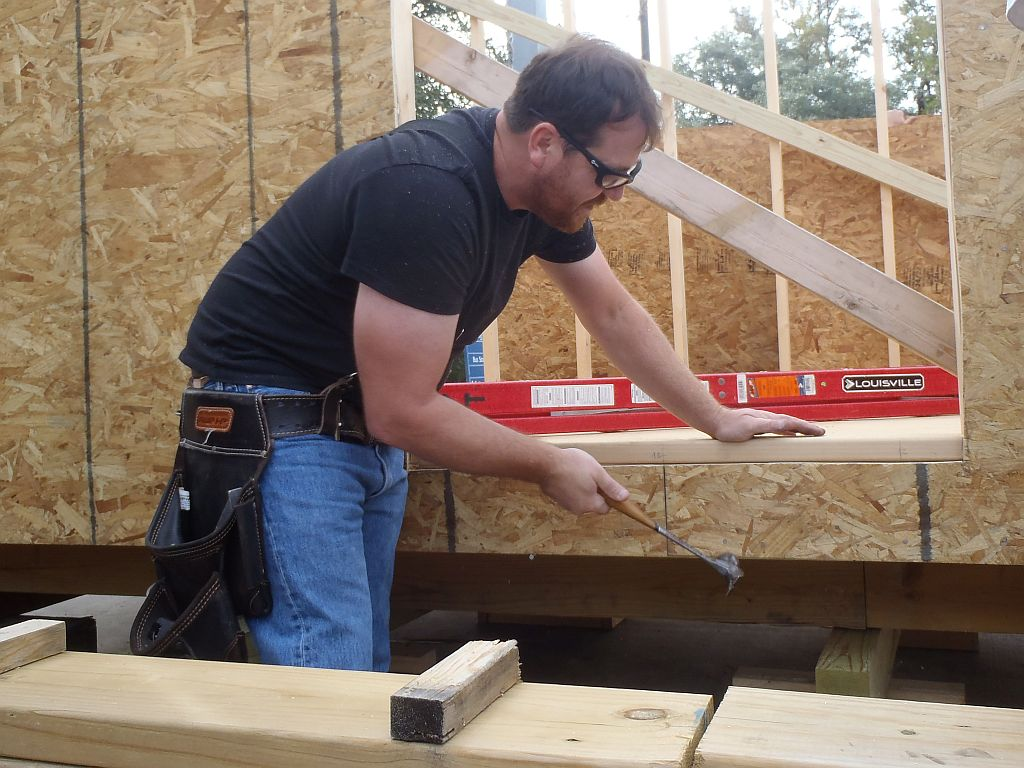 Student nailing OSB to frame