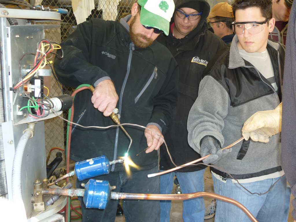 student solders copper line to HVAC compressor