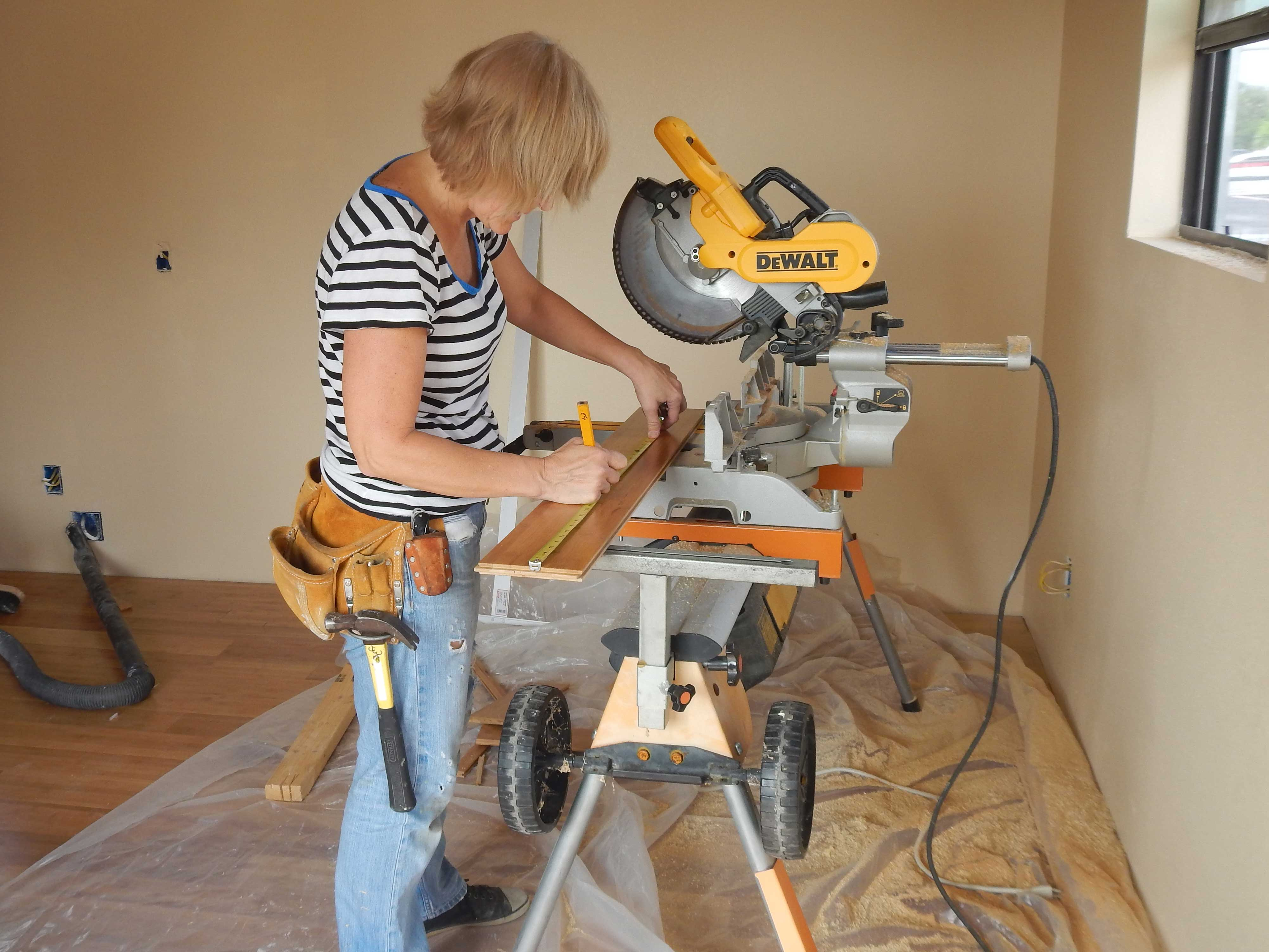 student marking wood floor plank to cut with chop saw