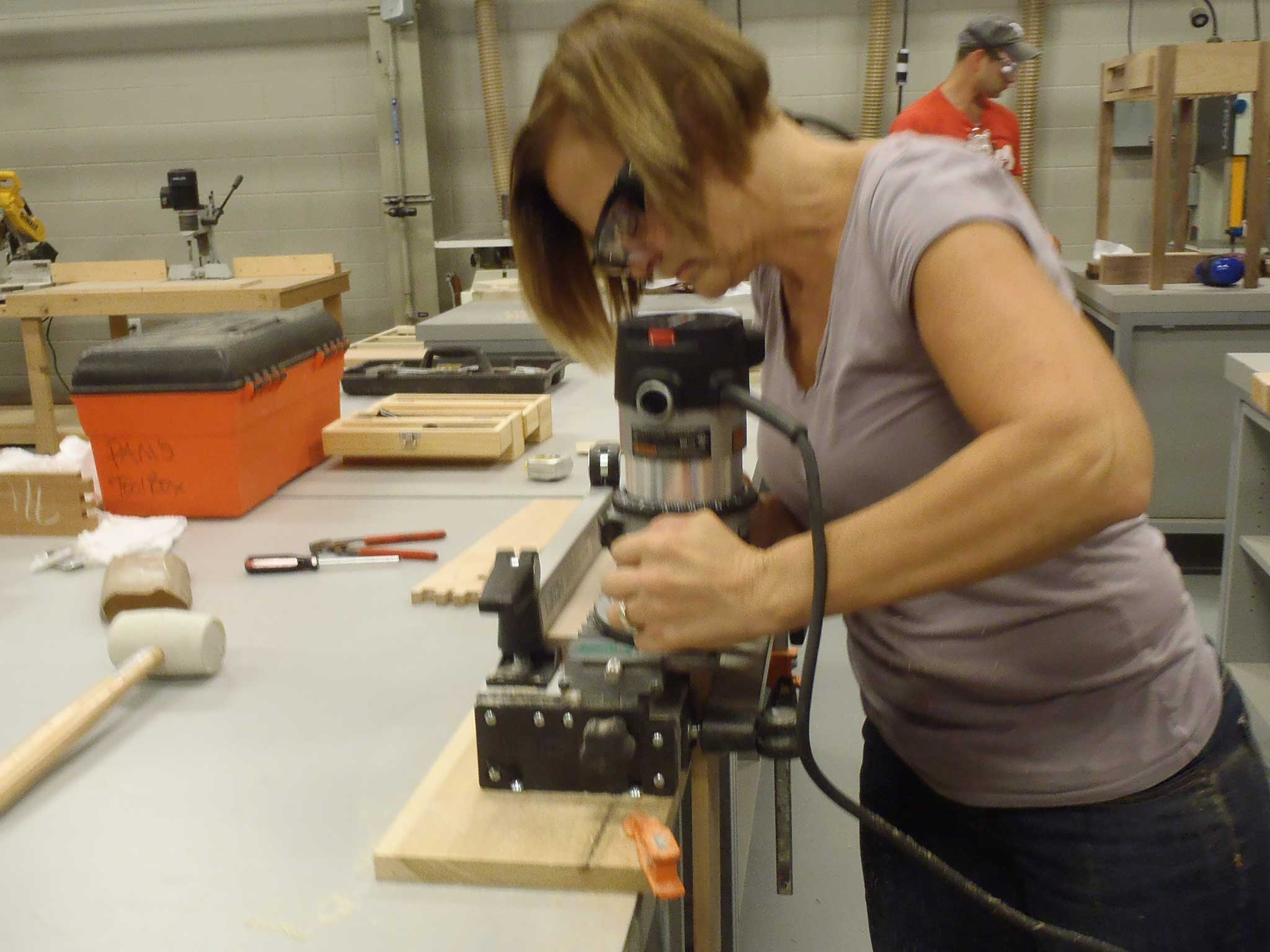 student using router with jigs for dovetail cuts