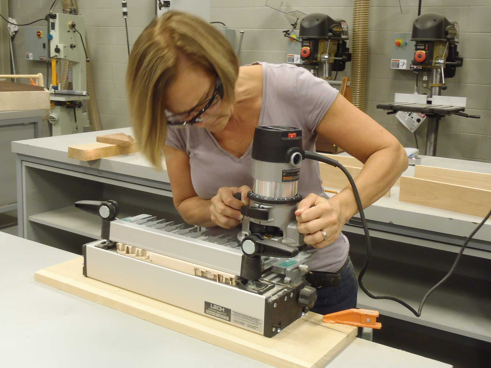 student using router to make dovetail cuts