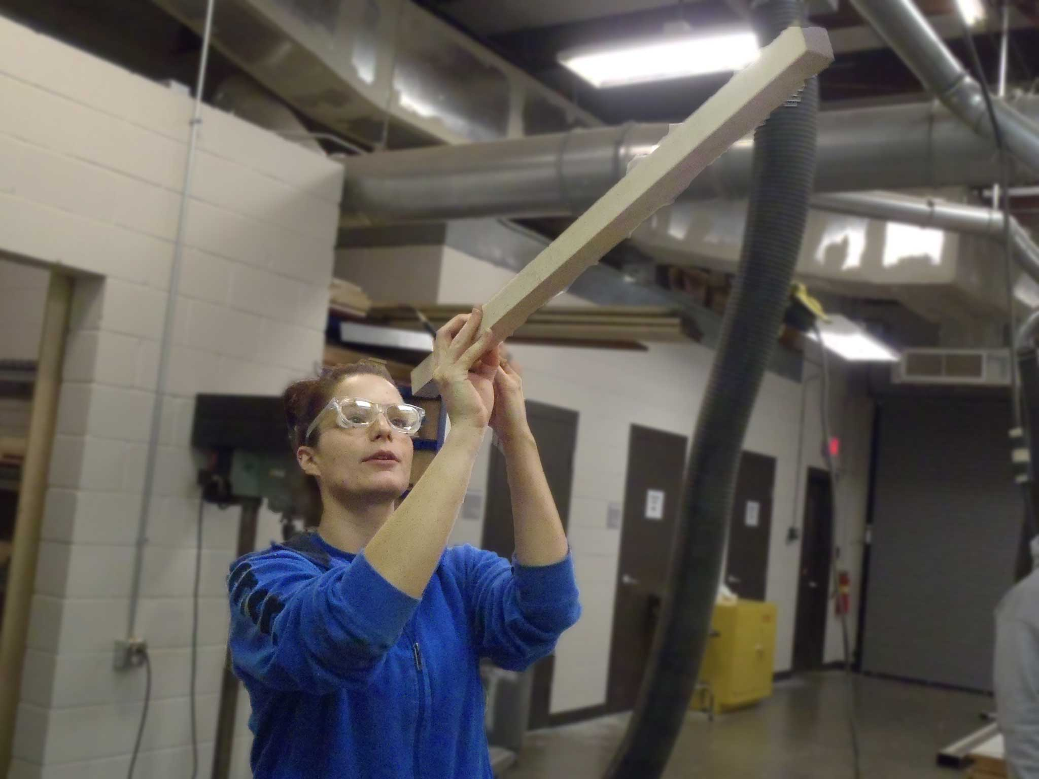 student checking wood for square