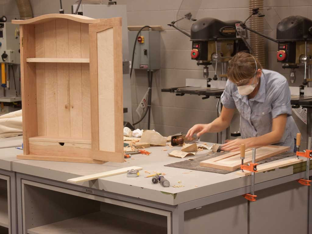 student working on hall cabinet