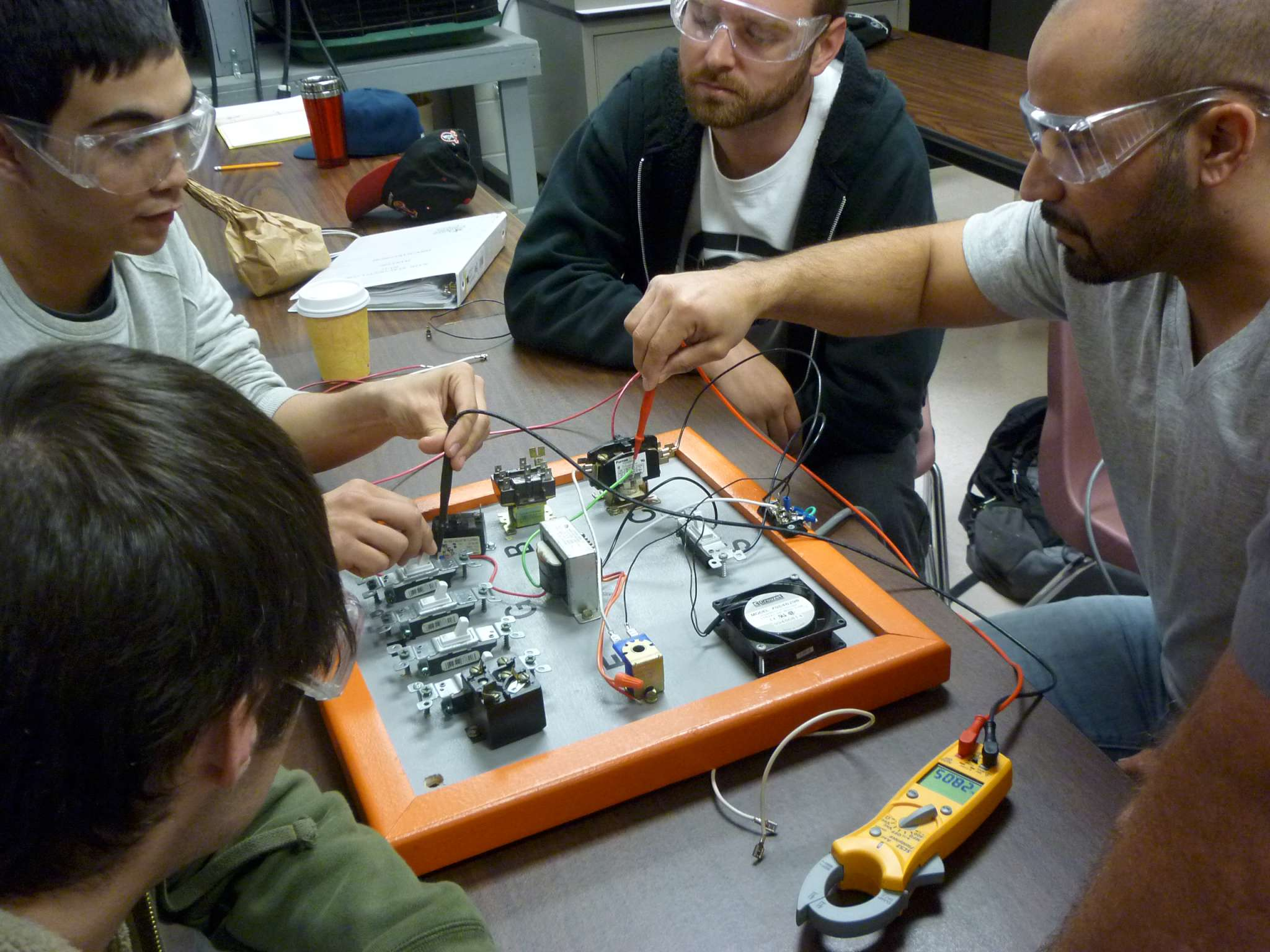 4 students taking various measurements on a circuit board