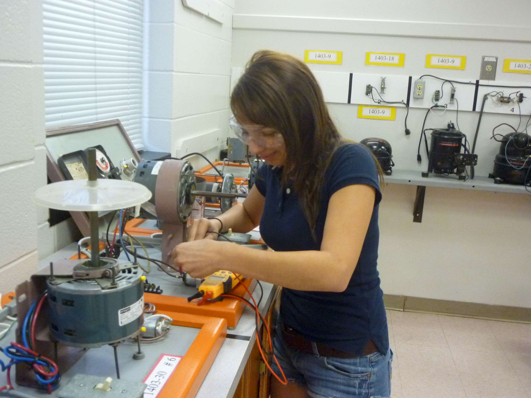 student measuring compressor with meter