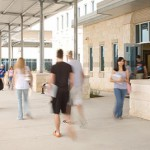 exterior of Cypress Creek Campus covered walkway with students passing by.
