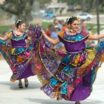 Ballet folklorico dancers in bright purple dresses with multi-colored shoulder and skirt layers performing in the South Austin Campus courtyard