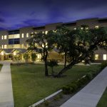 Exterior of South Austin Campus building and courtyard with large tree in far right side of the image. The campus and courtyard lamp posts are lit in the evening sky.