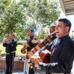 Four mariachi members playing instruments including guitars, a violin, a trumpet, and singing are performing in the South Austin Campus courtyard