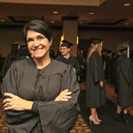 Annie Peck wearing black graduation robe smiles toward camera with arms slightly crossed