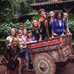 Group of smiling students crowded around a decorative rickshaw during a study abroad trip.