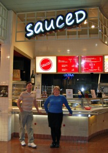 Annette Rhode and Carson Nunez stand in front of Sauced Pizza