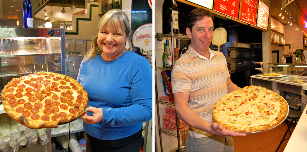 Sauced's owners proudly hold two of their handmade artisan pizzas